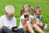 Happy little children playing in smartphones in the park. Brothers and sister.