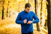 Man jogging in nature and checking pulse