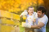 image of wooden fence  - Cute little boy and his father painting wooden fence together on sunny day in nature - JPG