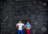 image of frot  - Cute boy and girl learning playfully in frot of a big blackboard - JPG