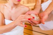 Couple relaxing together in wellness spa sauna with ice to cool down