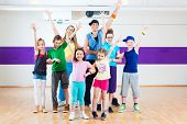 stock photo of zumba  - Dance teacher giving children Zumba fitness class in gym - JPG