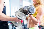 Man and woman in fitness gym lifting dumbbells looking at each other