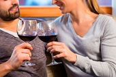 Young handsome couple drinking red wine at home