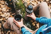 Traveler Woman Holding A Cup Of Tea And Thermos In Autumn Forest