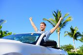Road trip travel - free man driving car in freedom. Happy young adult cheering in convertible for his summer vacations