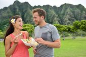 Hawaii food travel couple eating garlic shrimps on Oahu's North Shore. Popular Hawaiian shrimp food truck meal on road trip concept.