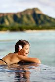 picture of waikiki  - Travel vacations woman on holiday at beach resort hotel pool - JPG