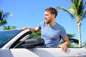 Hipster urban man portrait with cool convertible car on summer road trip. Young adult sitting in his rental new car looking happy.