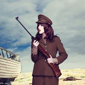 Attractive woman with long brunette hair in army uniform carrying a rifle standing on a beach with an old wooden boat alongside, square format