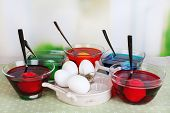 Eggs with liquid colour in glass on table on bright background
