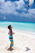 Little boy and a flock of seagulls at Caribbean beach