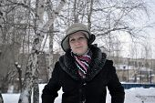 The Woman In A Hat And A Sheepskin Coat Costs In Park In The Winter.