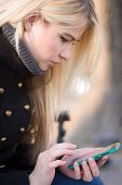 Young woman typing on phone.