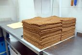 Empty chocolate shortcakes lay on the metal table. �?��?�¡ulinary workshop