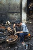 BANGKOK, THAILAND - DECEMBER 25, 2014: Street Photography of  auto  mechanic repairs old rims.