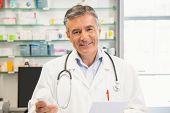 Happy pharmacist smiling at camera at the hospital pharmacy