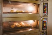 Bread rolls baking in oven in a commercial kitchen