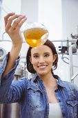 Woman looking at camera while holding beaker of beer in the factory