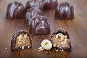 foto of bonbon  - Tasty chocolate bonbons cut in half with hazelnuts and cream inside - JPG