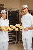 Team of bakers holding rack of rolls in a commercial kitchen