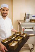 Happy baker holding tray of loaf tins in a commercial kitchen