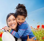 people, happiness, love, family and motherhood concept - happy mother and daughter hugging over blue sky and poppy field background