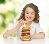 junk food, unhealthy eating, children and people concept happy smiling girl eating buns, donuts and burger over green background