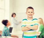 childhood, school, education and people concept - smiling little boy in casual clothes with crossed arms over group of students in classroom