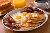 image of orange  - A delicious home style breakfast with crispy bacon eggs pancakes toast coffee and orange juice.