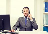 business, communication, technology and call center concept - friendly male helpline operator with headphones and computer at call center