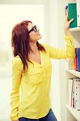 education concept - smiling redhead female student in eyeglasses choosing book in library