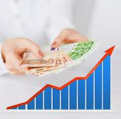 business, people and finances concept - close up of woman hands holding euro money over gray background with growth chart