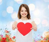 love, charity, holidays, children and people concept - smiling little girl with red heart over blue lights and poppy field background