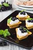 pic of mountain-ash  - canape with cottage cheese black berries of mountain ash and fresh mint leaves on a white wooden background - JPG