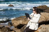 Attractive Woman Posing At The Seaside With Tablet