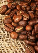 Roasted Coffee Beans On Burlap Background.