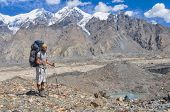 picture of shan  - Young hiker with large backpack on Engilchek glacier with scenic Tian Shan mountain range in Kyrgyzstan - JPG