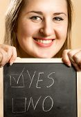 Portrait Of Smiling Woman Holding Board With Two Answers