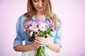 Fragile female looking at floral bouquet