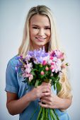 Charming blond girl with fresh flowers
