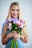Smiling female with flowers looking at camera