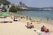 Tourists sunbathe at the Stanley town beach in Hong Kong, China.