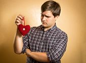 Handsome Man Looking Suspiciously On Decorative Red Heart