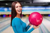 pic of bowling ball  - Beautiful young women holding a bowling ball while standing against bowling alleys - JPG