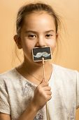 Smiling Girl Posing With Artificial Mustaches On Stick