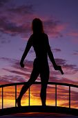 Silhouette Of A Woman With A Gun Down Walking