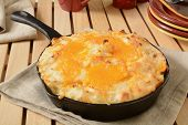 stock photo of shepherds  - Shepherds pie in a cast iron skillet with serving plates in background - JPG