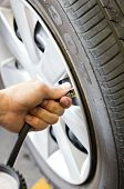 Man's Hand Checking Tyre Pressure.