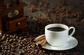 pic of cinnamon  - cup of black coffee with cinnamon sticks and coffee beans around - JPG